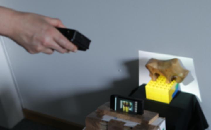 Abb. 1: Eine Szene wird von einem Benutzer aufgenommen. Der Projektor wird in der Hand gehalten um die Objekte zu Beleuchten. Das Smartphone nimmt die Szene auf und zeigt sie auf dem Bildschirm an