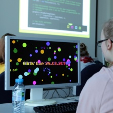 A girl, sitting in front of a computer screen, coding her individual screen saver.