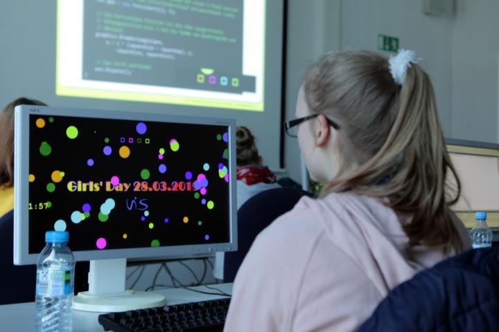 Ein Mädchen sitzt vor einem Computerbildschirm und kreiert ihren eigenen Bildschirmschoner.